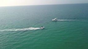 Luftvideoaufnahme mit Brummen über dem Meer und Strand mit Boot und Yacht stock video footage