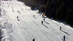 Luftvideoclip von den Leuten, die auf einem sonnigen Winterberg Ski fahren stock video footage