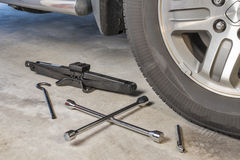 Lug wrench and car jack in a garage Stock Image