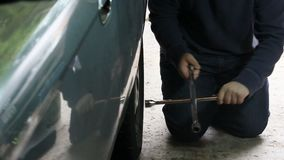 Lug wrench turning nuts on tire. Removing nuts from old tire stock video footage