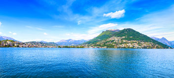 Lugano Lake panoramic landscape. City and mountains. Ticino, Swiss, Europe. Lugano Lake panoramic landscape. City, lake water, blue sky and mountains. Ticino Stock Photo