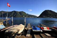 Lugano Lake with Swiss flag and boats Stock Photo