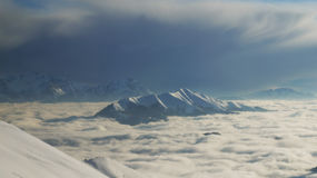 Lugano lake under cloud layer. View from mountain top to the alps, a cloud layer and a snowstorm coming up Royalty Free Stock Images