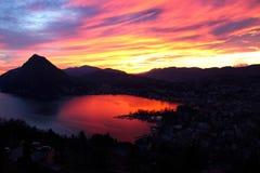 Lugano och Ceresio sjö på solnedgången arkivbild