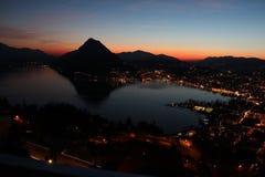 Lugano och Ceresio sjö på solnedgången royaltyfri foto