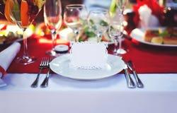 Lugar adornado hermoso en la tabla con la tarjeta de la huésped el día de fiesta, espacio vacío de la copia Fotografía de archivo