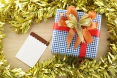 Lugar azul de la caja de regalo cerca de la nota de papel vacía en la madera de la decoración Foto de archivo