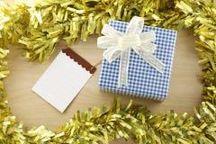Lugar azul de la caja de regalo cerca de la nota de papel vacía en la madera de la decoración Fotografía de archivo