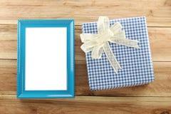 Lugar azul de la caja de regalo cerca del marco de madera azul en el piso de madera Fotografía de archivo