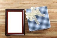 Lugar azul de la caja de regalo cerca del marco de madera de Brown en el piso de madera Imagen de archivo