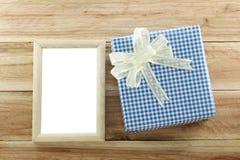 Lugar azul de la caja de regalo cerca del marco de madera en el piso de madera Fotos de archivo