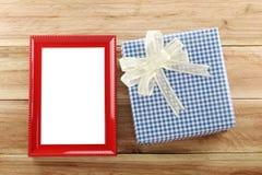Lugar azul de la caja de regalo cerca del marco de madera rojo en el piso de madera Imágenes de archivo libres de regalías