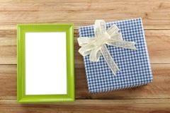 Lugar azul de la caja de regalo cerca del marco de madera verde en el piso de madera Fotos de archivo libres de regalías