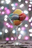 Lugar colorido de los macarrones en un vidrio del champán imagen de archivo