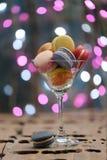 Lugar colorido de los macarrones en un vidrio del champán imagen de archivo libre de regalías