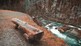 Lugar de descanso perto do rio, que corre através das montanhas Banco de madeira velho do ponto de vista do rio Vista da parte su filme