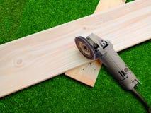 Lugar de la amoladora de ángulo en un tablón de madera Foto de archivo libre de regalías
