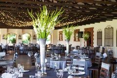 Lugar de la recepción nupcial con las tablas y las luces de hadas adornadas Fotos de archivo