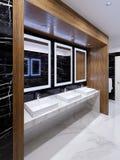Lugar de madera con los espejos, las luces y los fregaderos en la pared del mármol negro en un retrete público imagen de archivo libre de regalías