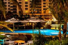 Lugar de relajación por la piscina durante noche foto de archivo