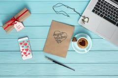 Lugar de trabajo acogedor en la endecha plana de madera el día de tarjetas del día de San Valentín Imagen de archivo