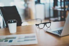Lugar de trabajo cómodo Primer del lugar de trabajo cómodo en oficina con la tabla de madera y el ordenador portátil que ponen en imagen de archivo libre de regalías