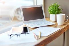 Lugar de trabajo cerca de la ventana con el ordenador portátil y el ordenador Copie el espacio Fotos de archivo libres de regalías