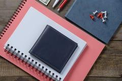 Lugar de trabajo con el dinero, cartera de cuero elegante, cosas del negocio, pluma, cuaderno en la tabla de madera Imágenes de archivo libres de regalías