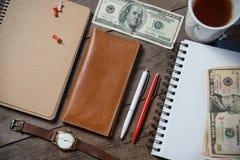 Lugar de trabajo con el dinero, cartera de cuero elegante, cosas del negocio, pluma, cuaderno en la tabla de madera Fotografía de archivo libre de regalías