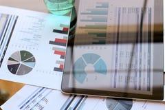 Lugar de trabajo con el ordenador portátil, tableta digital; gráficos en la oficina imágenes de archivo libres de regalías