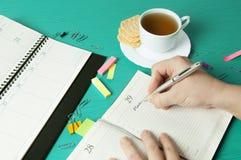 Lugar de trabajo con el organizador, la pluma, el lápiz, las galletas y la taza de té Imagen de archivo