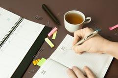 Lugar de trabajo con el organizador, la pluma, el lápiz y la taza de té Fotografía de archivo