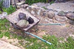 Lugar de trabajo con la carretilla y piedra en granja Fotos de archivo