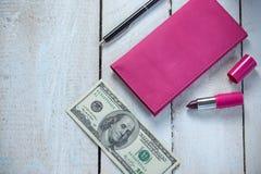 Lugar de trabajo con la cartera, el dinero, la pluma y el lápiz labial de cuero rosados en la tabla de madera blanca Foto de archivo
