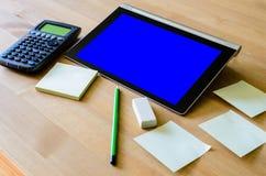 Lugar de trabajo con la PC de la tableta - caja azul, calculadora, lápiz y stic Fotos de archivo libres de regalías