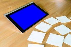 Lugar de trabajo con la PC de la tableta - caja azul - y varias notas pegajosas Foto de archivo libre de regalías