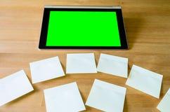 Lugar de trabajo con la PC de la tableta - caja verde - y varias notas pegajosas Imagen de archivo libre de regalías
