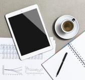 Lugar de trabajo con la tableta, el café, el cuaderno y la pluma digitales en blanco en la tabla hecha del granito foto de archivo