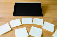 Lugar de trabajo con PC de la tableta y varias notas pegajosas Imágenes de archivo libres de regalías