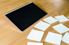 Lugar de trabajo con PC de la tableta y varias notas pegajosas Foto de archivo libre de regalías