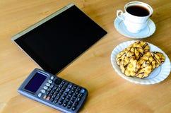 Lugar de trabajo con PC, la calculadora, la taza de café y las galletas de la tableta Imagenes de archivo