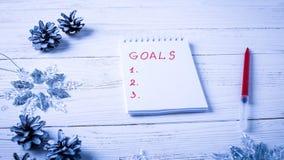 Lugar de trabajo con un diario, las decoraciones y los regalos Lista o del ` s del Año Nuevo imagenes de archivo
