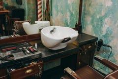 Lugar de trabajo con un lavabo en barbería Interior del salón de belleza de lujo imagenes de archivo