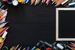 Lugar de trabajo creativo con los lápices multicolores, las pinturas, el marco y otras fuentes de escuela en el escritorio negro, imagen de archivo libre de regalías