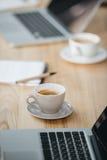 Lugar de trabajo de la oficina con café y ordenadores portátiles imagen de archivo