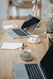 Lugar de trabajo de la oficina con café y ordenadores portátiles imágenes de archivo libres de regalías