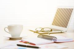Lugar de trabajo de la oficina con el ordenador portátil, el café e informes Fotografía de archivo libre de regalías