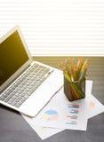 Lugar de trabajo de la oficina con el ordenador portátil, informes y lápices Fotografía de archivo libre de regalías