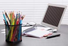Lugar de trabajo de la oficina con el ordenador portátil, informes y lápices Foto de archivo