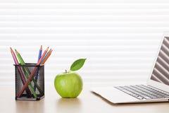 Lugar de trabajo de la oficina con el ordenador portátil, la manzana y los lápices Imagen de archivo